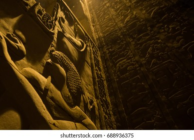 Dark dimly lit temple in egypt at night, with heavy shadows emphasizing hieroglyphics