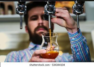 Dark draft beer poured by bartender