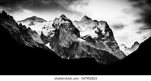 Dark dramatic mountain range with snow on peaks - Black and white monochrome