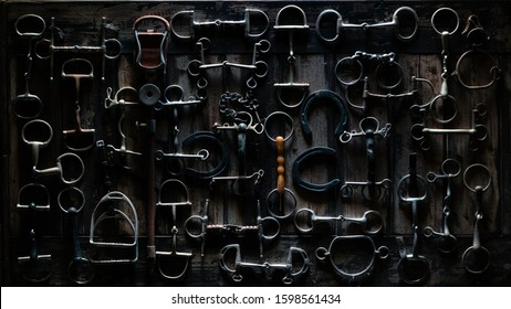 A dark & dramatic photo of horse tack on a wooden table.