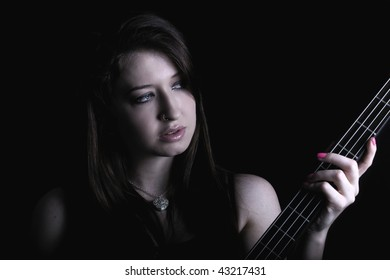 a dark and dramatic shot of a young woman with a bass guitar