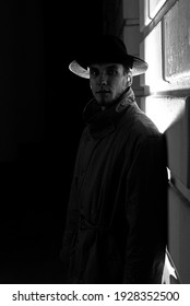 dark dramatic silhouette of a man in a hat and raincoat at night on the street in Noir style
