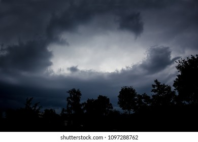 Dark dramatic dark sky and black silhouettes of trees. Stormy weather on summer day