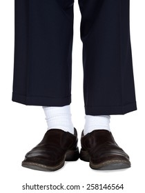 Dark dress pants with white socks and brown loafers.