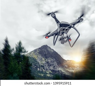 Dark drone in the air against the backdrop of a mountain landscape.