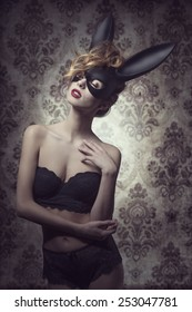 Dark easter portrait of sensual curly woman with romantic expression posing with mysterious bunny mask and lace lingerie