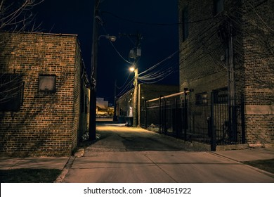 Dark and eerie urban city alley with vintage warehouses and factory buildings at night