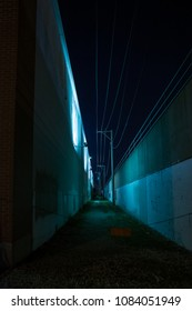 Dark and eerie urban city alley with tall walls at night