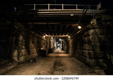 Dark and eerie urban city alley with vintage railway bridge and tunnel at night
