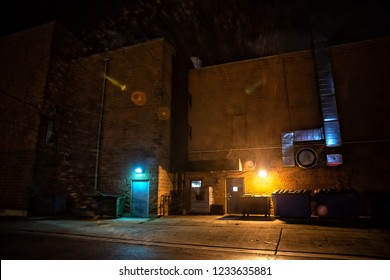Dark and eerie urban city alley with dumpsters and doors at night