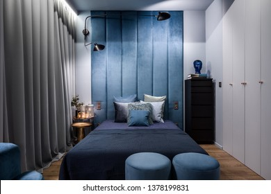 Dark and elegant bedroom with double bed and upholstered wall