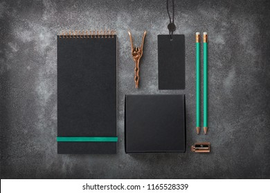 dark elegant branding / identity mockup with blank notebook, black cardboard box for packaging purposes, tag with metal seal, copper utensils, turquoise details / accents - top view