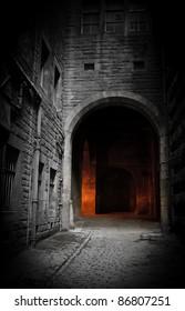Dark empty courtyard in Edinburgh, Scotland with mysterious glowing archway