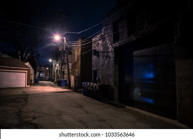 Dark empty and scary urban city streetalley with vintage buildings and garbage cans at night
