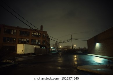 Dark and empty urban city parking lot with a vintage industrial warehouse factory building and a truck semi-trailer at night