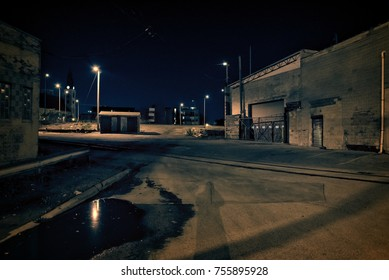 Dark factory warehouse alley with railroad tracks and rain puddle at night.