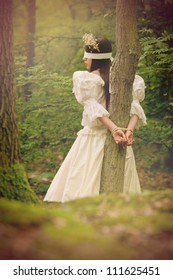 Dark fairytale inspired image, beautiful young woman in woods, tied with rope to a tree and blindfolded