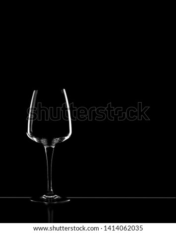 Dark field lighting technique used to hilight the edges of an empty wine glass and table on a black background. Copy space.