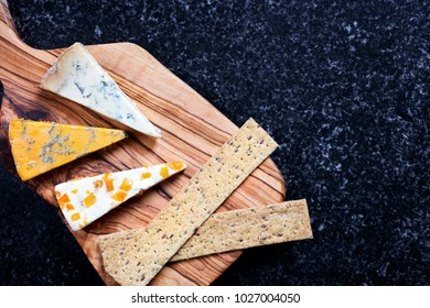Dark Food - Blue Stiltons and Blue Shropshire cheeses on an olive wood board - with copy space - overhead