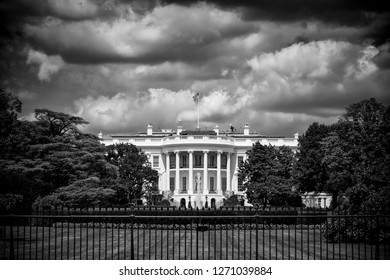 Dark and foreboding monochrome view of the White House with storm clouds brewing above the South Lawn in Washington DC, USA