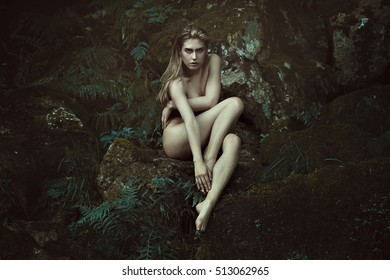Dark forest dryad posing on mossy rocks. Fantasy and myth