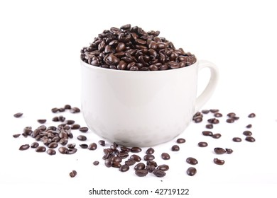 Dark French Roasted Coffee beans in a large white cup spilling over onto the white backgorund.
