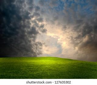 Dark gloomy evening with a bright lush meadow