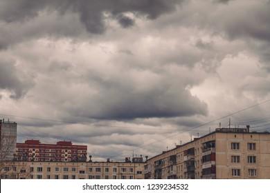 Dark, gloomy overcast sky over buildings in city during thunderstorm