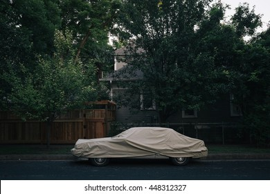 A dark, gloomy photo of an abandoned, covered car on a residential street, subdued tones