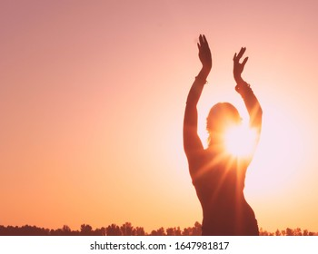 dark glowing silhouette of slim woman with hands up in the air illuminated with sunshine dancing traditional tribal belly dance in front of aurora sky at sunrise