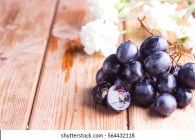 dark grape and white flower on wooden table