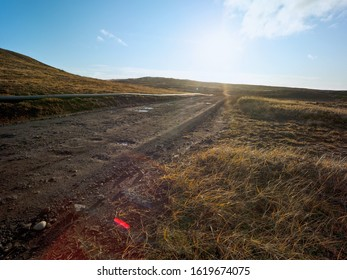 Dark gravel road in a volcanic landscape with grass and moss in Iceland. Pipeline next to gravel road. Backplate for 4x4 4WD offroad cars and also for trekking and hiking. Lense flare.