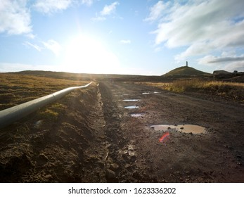 Dark gravel road in a volcanic landscape with grass and moss in Iceland. Pipeline next to gravel road. Backplate for 4x4 4WD offroad cars and also for trekking and hiking. Lense flare Puddles in the g