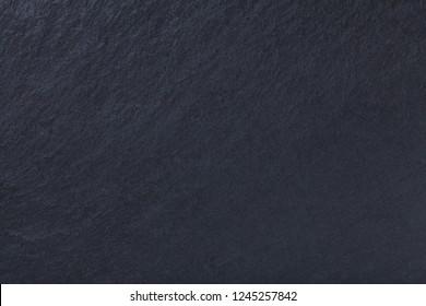 Dark gray background of natural slate. Texture black stone close up. Graphite backdrop macro