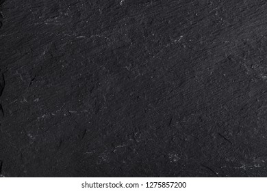 Dark gray black slate background or texture of natural stone. Black board for serving close-up