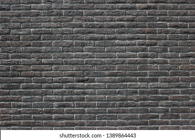 Dark gray brick wall background texture with slightly purplish and earth tones colors details
