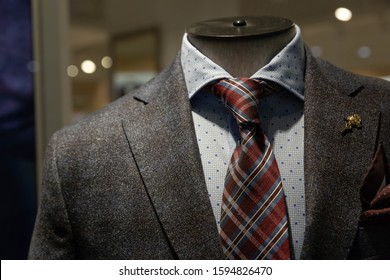 A dark gray jacket, a tie with blue and Burgundy stripes, a blue shirt with a pattern of squares hang on a mannequin behind glass in the window of a fashionable men's clothing store.