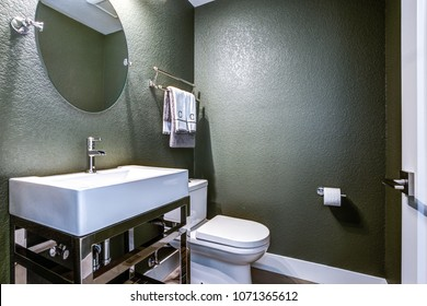 Dark Gray powder room features chrome washstand with white sink next to toilet.