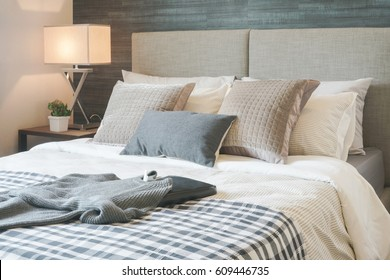 Dark gray sweater on bed with stylish bedroom interior
