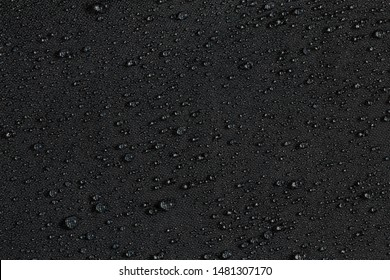 dark gray waterproof hydrophobic flat cloth closeup with rain drops background