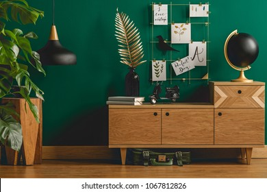 Dark green apartment interior with scandinavian style wooden furniture and designer black and gold decorations