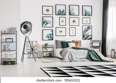 Dark green blanket lying on a king-size bed in a gallery themed bedroom interior