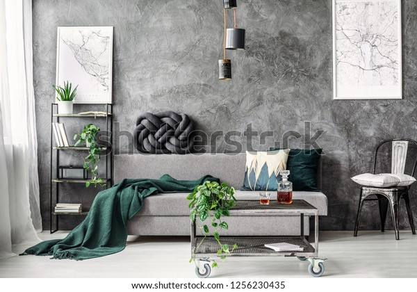 Dark green blanket on comfortable grey sofa in elegant industrial living room with maps on empty wall