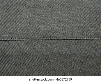 dark green fabric with khaki stitched her seam closeup