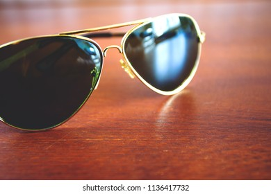 dark green and golden fashion sunglasses on the table, retro toned