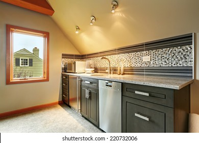 Dark green kitchen cabinets with back splash trim, steel appliances in small room with vaulted ceiling
