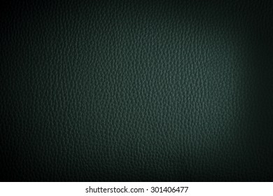dark green leather background or texture with dark vignette bord
