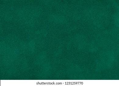 Dark green matte background of suede fabric, closeup.