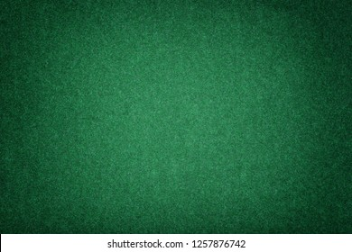 Dark green matte background of suede fabric, closeup. Velvet texture of seamless emerald woolen felt with vignette.
