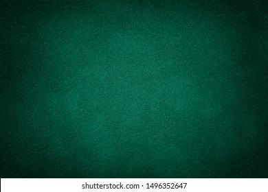 Dark green matte background of suede fabric, closeup. Velvet texture of seamless deep emerald leather. Felt material macro with vignette.